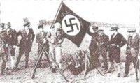 """""""Знамя """"Егерской ватаги"""" фон Гейдебрека (ок. 1924 г.).Чины фрейкора, одетые """"по гражданке"""", позируют на фоне """"свастичной"""" стороны своего знамени (изображение другой стороны знамени до нас не дошло)."""