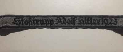 """Партийной свастичной """"боевой повязкой"""" с двусторонней черной каймой (как в будущем - у чинов СС) на левом рукаве выше локтевого сгиба."""